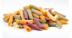 Heap of colored uncooked italian pasta penne on a white - stock photo