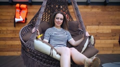 Young woman with striped T-shirt is sitting on big hanging lounger. Stock Footage