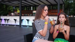 Mother with her daughter are sitting and drinking juice near bar. Stock Footage