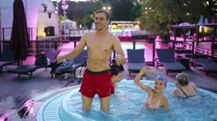 Young man and little girl are dancing on a pool at the evening. Stock Footage