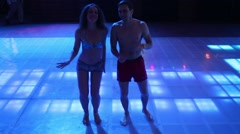 Two of man and woman in shorts are dancing on dancefloor Stock Footage