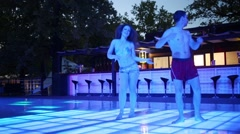 Two of man and woman in shorts are dancing on dancefloor near bar Stock Footage