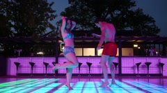 Two of man and woman in swimwear are jumping on dancefloor Stock Footage