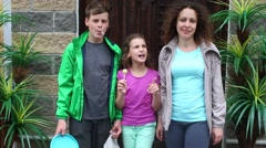 Mother and her children with lollipop are standing near palm Stock Footage