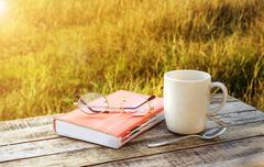Cup of coffee and note book on wooden table - stock photo