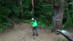 One little boy in jacket and boots is hanging on the long rope swing Stock Footage