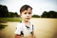 Portrait of boy standing in sand looking at camera - stock photo