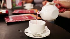 Teapot and teacup with herbal tea in cafe, close up view. Stock Footage