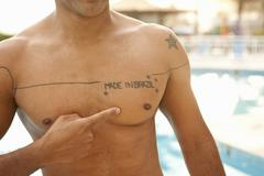 Cropped shot of man pointing to chest tattoo at hotel swimming pool, Rio De Stock Photos