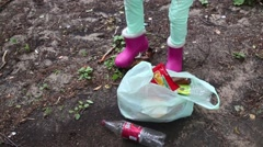 One little girl is pressing used bottle by foot and put it on bag Stock Footage