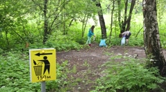 Two people are cleaning park by picking up trash to the bags. Stock Footage