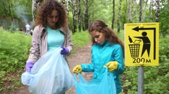 Two of the woman and little girl is standing with trash near sign Stock Footage