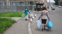 Three of the woman and children are holding bags with trash Stock Footage