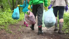 Three of the mother with children is holding trash bags and go away Stock Footage