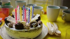 Birthday cake with many one-use dishes on the yellow table Stock Footage