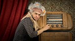 Grandmother turn on a radio and start listen music - stock footage