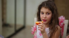 One beautiful girl with curly hair is sitting and eating orange. Stock Footage