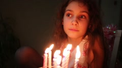Little girl with curly hair is making wish in front of birthday cake. Stock Footage