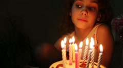 Little girl with a curly hair is blowing candles on birthday cake. Stock Footage
