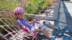 Girl in pink helmet and rollers lying in net hammock in skate park. Stock Footage