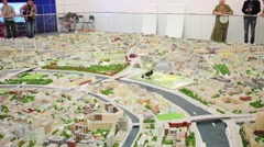 Small bird walking on miniature of center of Moscow and flying away Stock Footage