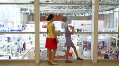 Woman and girl watching from second floor to halls exhibition Stock Footage