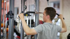 Guy pulling hands to handle with weight of fitness machine Stock Footage