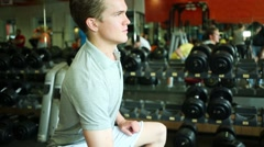 Man sitting at racks of dumbbells and shaking one in right hand Stock Footage