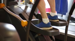 Man feet in sneakers on electronic elliptical trainer in fitness club Stock Footage