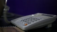 Hands taking handset and pressing button of white phone close up Stock Footage