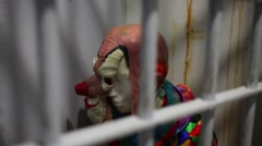 Mannequin with clown mask and clothes behind lattice door. Stock Footage