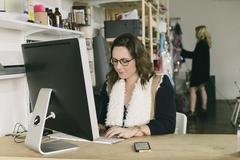 Female office worker at desk in design studio - stock photo