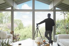 Rear view of man leaning on telescope looking out of window admiring garden - stock photo