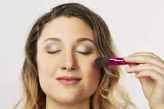 Young woman using blusher brush - stock photo