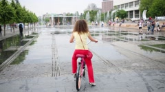 Woman on pink bike are not daring to go through jet of dry fountain Stock Footage
