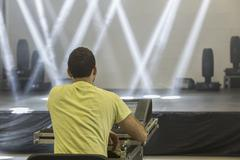Rear view of man with sound mixer sitting against illuminated stage - stock photo