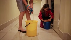 Boy and girl wiping floors in hallway with buckets. Stock Footage
