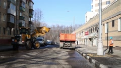Yellow excavator loading shovel snow remnants in truck on street. Stock Footage