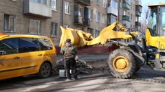 Yellow excavator removing with bucket remnants of snow on street Stock Footage