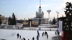Ice skating rink at VDNKh with people at central pavilion and fountain Stock Footage