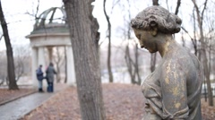 Dirty bronze sculpture of woman in park, next to gazebo and people. Stock Footage