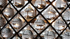 Close-up of lot of swinging glass balls hanging in square. Stock Footage