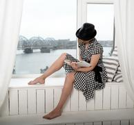 woman in black hat reading a book - stock photo