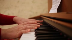 Close-up of womans hands in red playing piano in room. Stock Footage