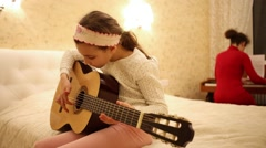 Girl playing guitar, sitting on bed, and mother playing piano behind. Arkistovideo
