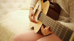 Girl on bed pulling strings of guitar in her hands. Stock Footage