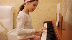 Girl playing piano few notes, then smiling and asking. Stock Footage