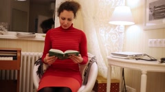 Woman in red dress is reading book by window at night. Stock Footage