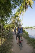 Rear view of two female tourists cycling on Mekong riverbank, Don Det, Laos - stock photo