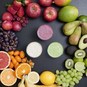 Overhead still life of variety of fruit surrounding fresh smoothies - stock photo